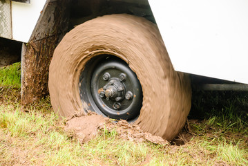 Wheel of a truck lorry spinning as it is stuck in deep mud soft grass
