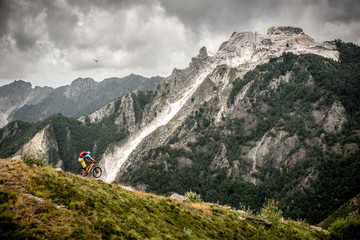 Tuscany Mountain biker wheelies down a steep ridge with epic marble mountain behind and eagle above