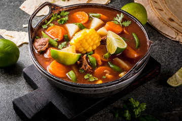 Autumnal vegetable stew. Mexican traditional vegetable soup Mole de olla with meat, potatoes, carrots, beans, corn and lime. Copy space
