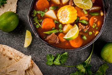 Autumnal vegetable stew. Mexican traditional vegetable soup Mole de olla with meat, potatoes, carrots, beans, corn and lime. Copy space top view