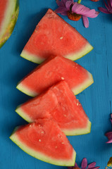 slices of fresh watermelon with pink garden flowers on turquoise blue painted wood