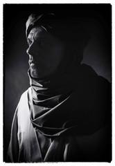 Vintage black and white profile photo of berber man in night light wearing turban with robe. Studio shot.