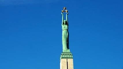 grüne weibliche Figur der lettischen Freiheitsstatue vor tiefblauen Himmel in Riga