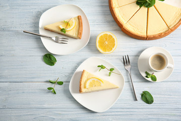 Plates with delicious cheesecake and cup of coffee on wooden table