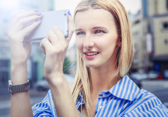 Blonde-haired girl, taking  pictures on smartphone, holding it with both hands, Day, outdoor. Woman in blue striped shirt , smiling