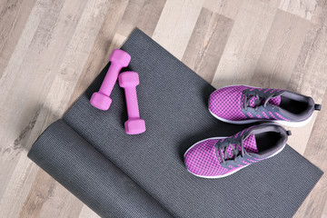Yoga mat, sneakers and dumbbells on wooden floor