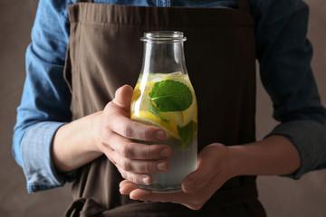 Young woman holding bottle of fresh lemonade, closeup