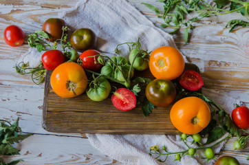Composition of bright tomatoes on wooden background. Flatlay. Top view.