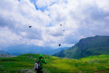 A guy is photographing black birds flying in the mountains, Alps, Italy. The landscape is represented by mountains and green meadows in a cloudy day