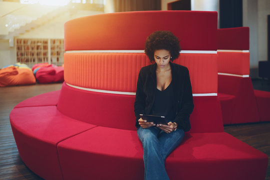Young serious afro american girl with curly hair is sitting on red curved sofa in chillout office space and reading e-mail from her boss about future meeting with copy space place for text or logo