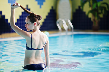 Portrait of a pretty girl wearing bikini in a pool in the water park with tiled walls in the background.