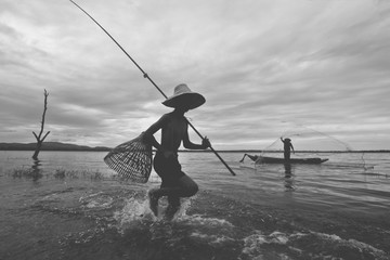 Fisherman boy and his granfather catching fish with equipment, Black and White vintage film tone,...