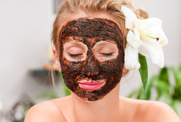 Spa salon. Beautiful woman with facial mask at beauty salon