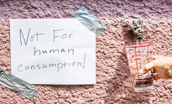 """horizontal image of a sign saying """"not for human consumption"""" beside an outdoor water tap with a glass being filled with the contaminated water."""