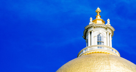 Golden dome of Massachusetts State House under blue sky
