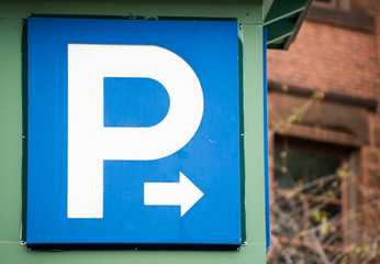 blue and white parking sign with arrow pointing right
