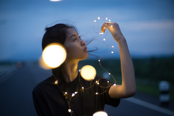 Young woman with fairy light