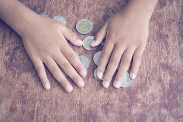 Financial education concept with child hands putting over on coins on the wooden table, Silver Thai coins
