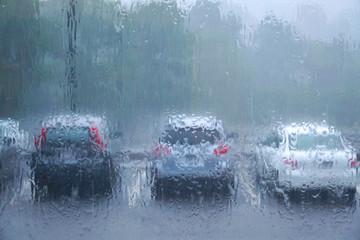 cars in a row in parking lot in heavy rain through window
