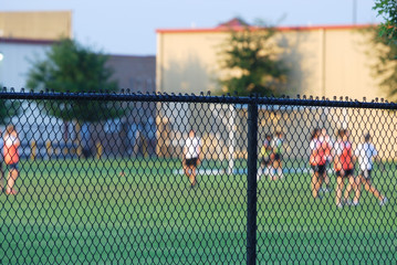 football field and players behind chain link fence