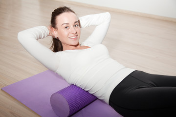 attractive girl coach demonstrates exercises myofascial relaxation on the foam roller