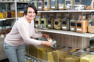 Mature  woman standing next to jars with dried cereals