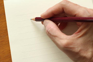 便箋とペンを持つ手
