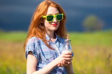 Redhead skinny girl in sunglasses holding milkshake