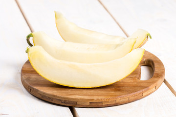 Three slices of fresh melon on the wooden round board