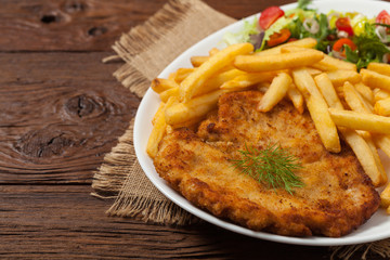 Chicken schnitzel, served with fries and salad.