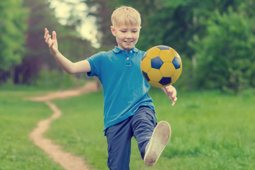 Blond boy in a blue T-shirt kicking a ball on a forest path