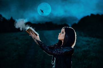 A young witch in a black dress conjures at night on a full moon. Fantasy illustration. Fairy tale