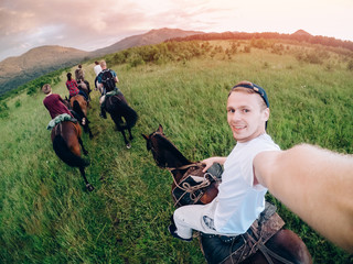 male rider on horseback holds a camera in his hand and takes a picture of Selfie.