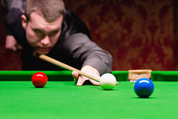 Male snooker player playing snooker game