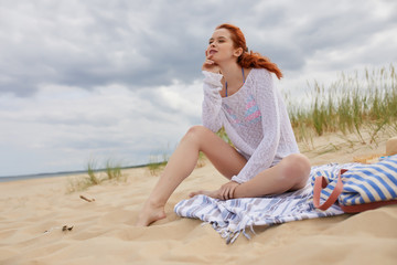 Red-head girl at the beach in sunrise.
