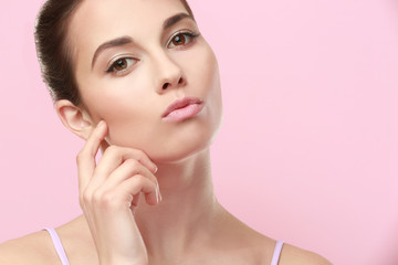 Closeup view of beautiful young woman with natural lips makeup touching face on color background