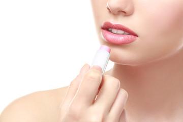 Closeup view of beautiful young woman applying lipstick, white background