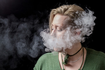 Young woman exhaling nicotine smoke from electronic cigarette
