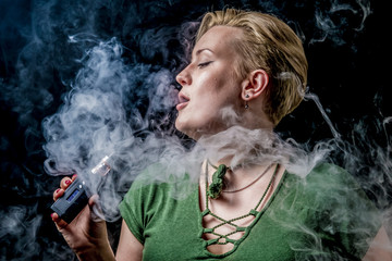 Female exhaling smoke and smoking electronic cigarette
