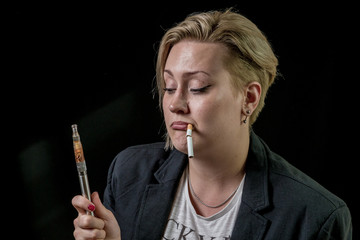 Female is questioning about vaping electronic cigarette while holding tobacco cigarette between her teeth