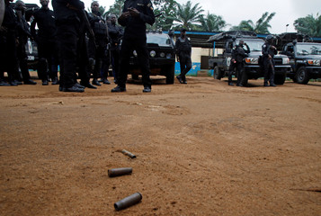 Bullet casings are seen on the ground as policemen stand at the National Police Academy in the Cocody neighborhood in Abidjan