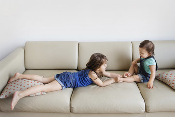 Young boy and girl playing on a sofa.