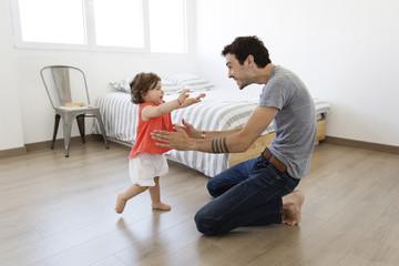 Man kneeling on hardwood floor, playing with baby girl
