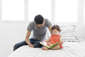 Tattooed man wearing grey T-shirt and jeans and baby girl in red dress sitting on bed with stripy duvet, looking at book.