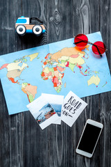 accessories for treveling with children, telephone, map and photos on dark woode background top view mock-up