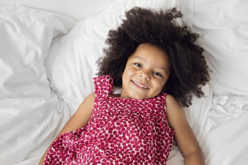 Portrait of girl with curly hair lying on bed