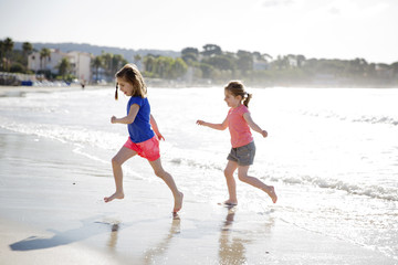 Two girls wearing shorts playing on a sandy beach, running.