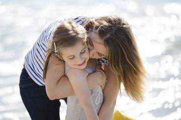 Blond woman wearing stripy T-shirt standing on beach, hugging girl.