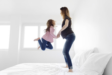 Pregnant woman and girl jumping on a bed.