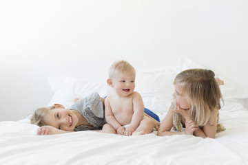 Two girls and baby boy on bed